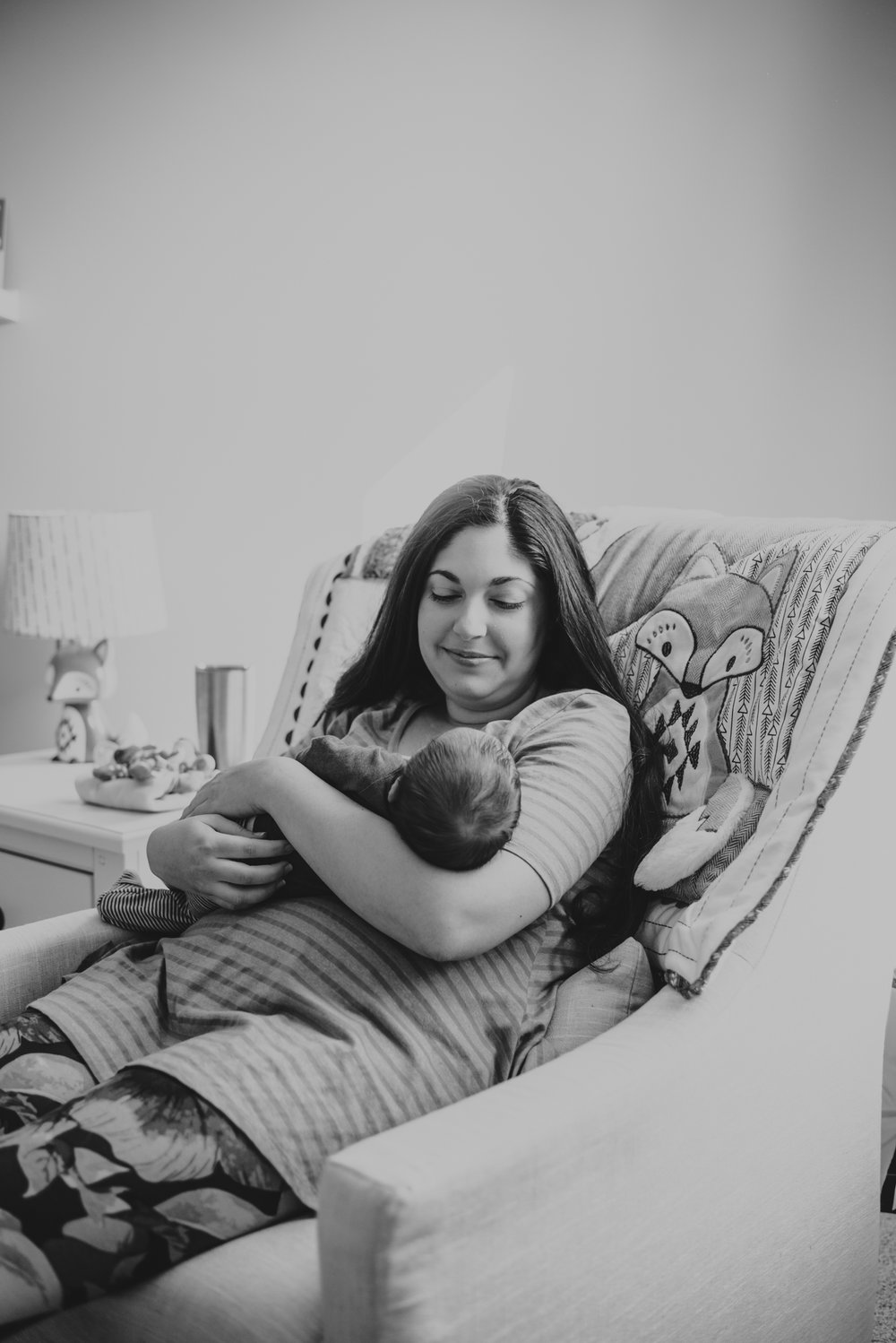 The new Mom cuddles her newborn son in a chair in the nursery in Wake Forest, a black and white image by Rose Trail Images.