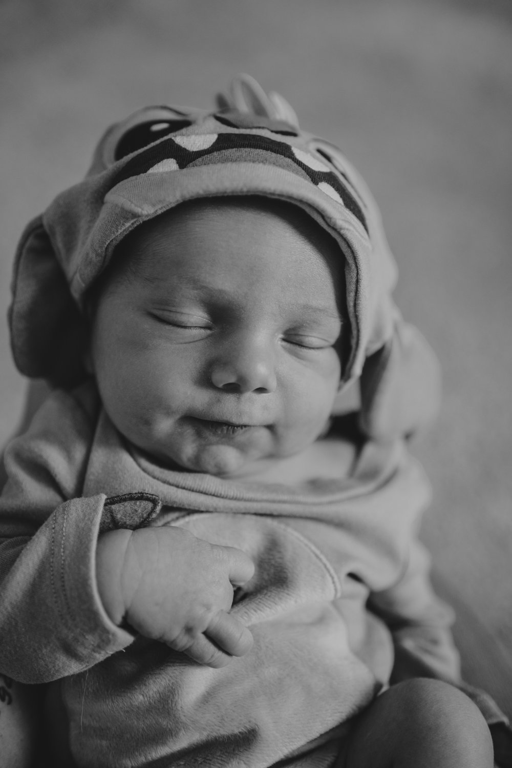 The newborn baby sleeps dressed as the Disney character Stitch while in his nursery in Wake Forest, a black and white image by Rose Trail Images.