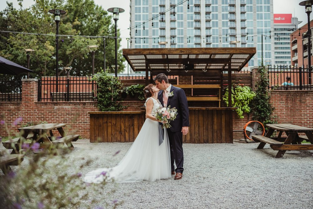 The bride and groom kiss on the patio after their wedding ceremony at Caffe Luna in downtown Raleigh, NC, photo by Rose Trail Images.