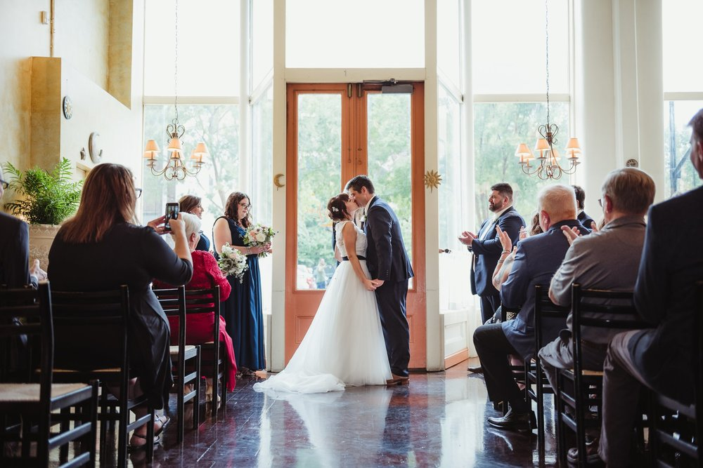 The bride and groom exchanged their first kiss as husband and wife during their wedding ceremony, pictures taken by Rose Trail Images at Caffe Luna in Raleigh, NC.
