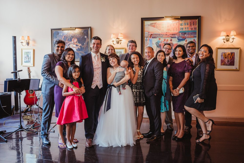 Some of the guests got together with the bride and groom for a group picture during the wedding reception at Caffe Luna, pictures taken by Rose Trail Images in Raleigh, NC.