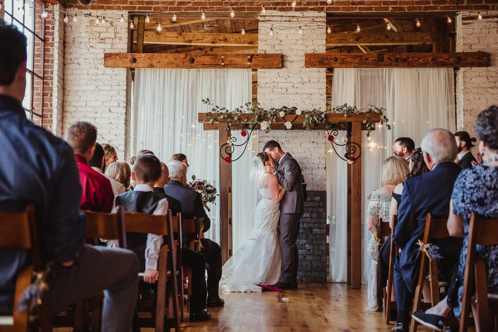The bride and groom share their first kiss as husband and wife during their wedding ceremony in Raleigh, North Carolina, pictures by Rose Trail Images.