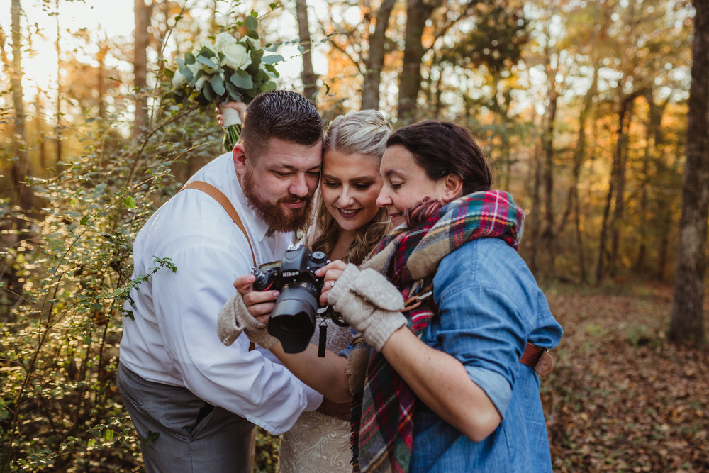 Audrey, photographer of Rose Trail Images, gets excited and shows an image from the back of her camera to a bride and groom.