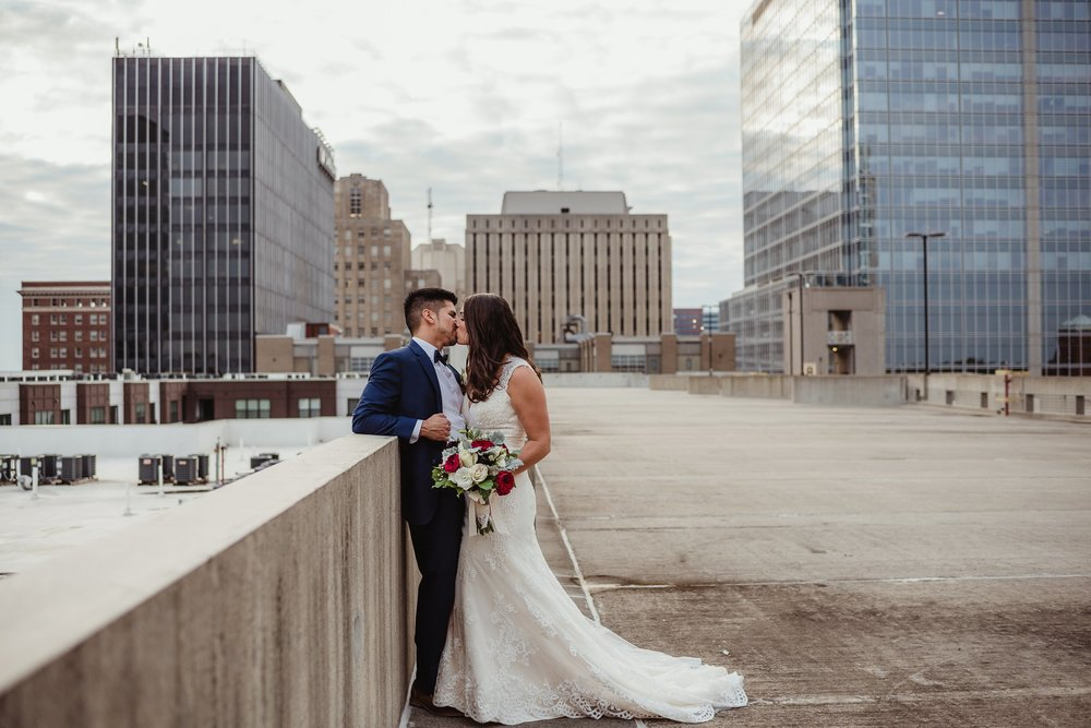 The bride and groom kiss on a rooftop after their wedding ceremony in downtown Raleigh, photo by Rose Trail Images.