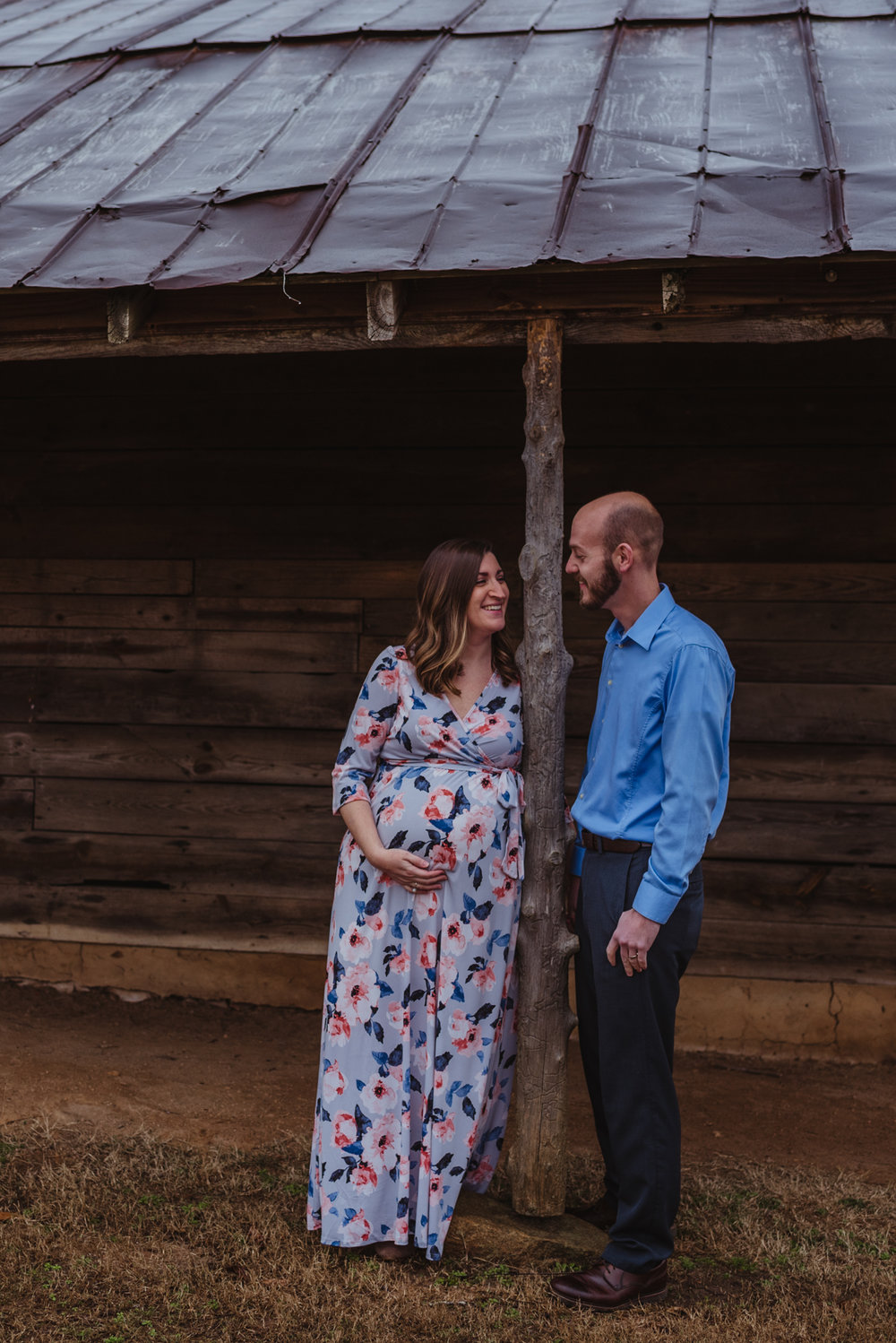 The parents to be laugh together under the old barn, picture taken by Rose Trail Images at Joyner Park in Wake Forest, NC.