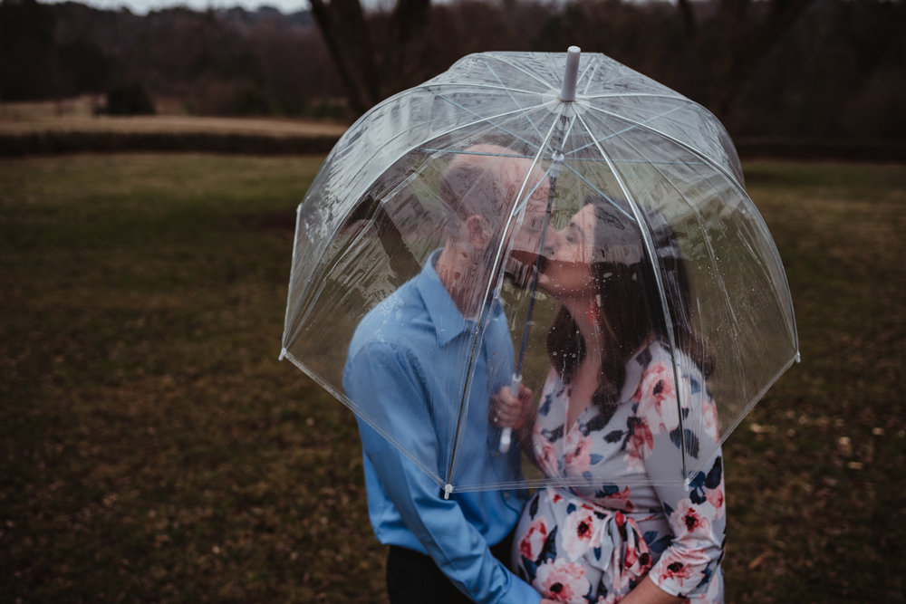 The parents to be kiss under an umbrella, picture taken by Rose Trail Images at Joyner Park in Wake Forest, NC.