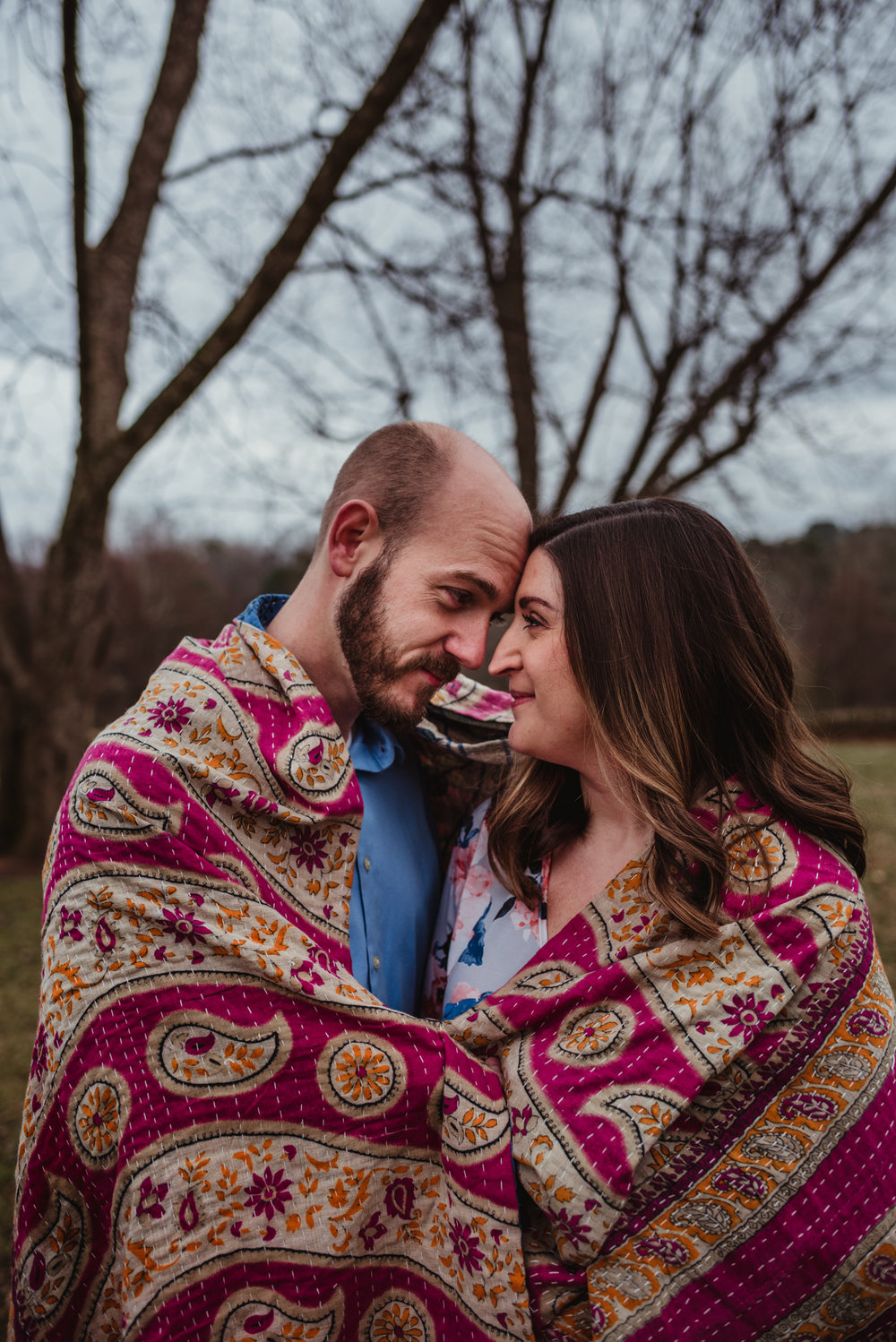 The parents to be snuggle together under a pink blanket, picture taken by Rose Trail Images at Joyner Park in Wake Forest, NC.