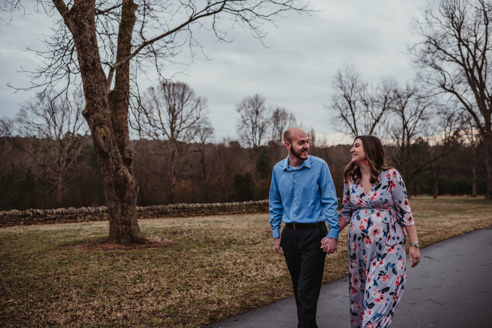 The parents to be walk together in the pecan grove, picture taken by Rose Trail Images at Joyner Park in Wake Forest, NC.