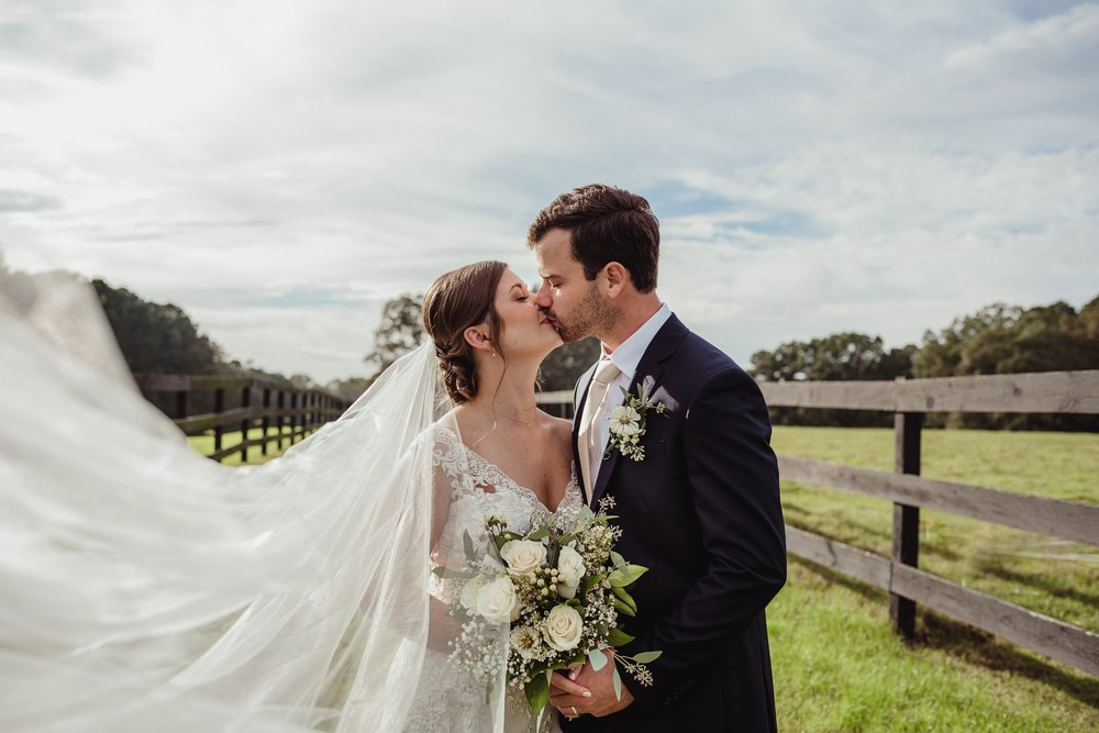 A bride and groom kiss outdoors after their wedding ceremony in Raleigh, North Carolina. Photo by Rose Trail Images.