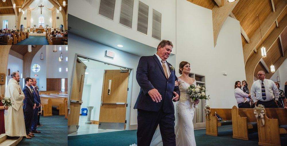The bride walks down the aisle to her groom at their wedding ceremony at Saint Bernadette's Catholic Church in Fuquay Varina, North Carolina. Photo by Rose Trail Images.