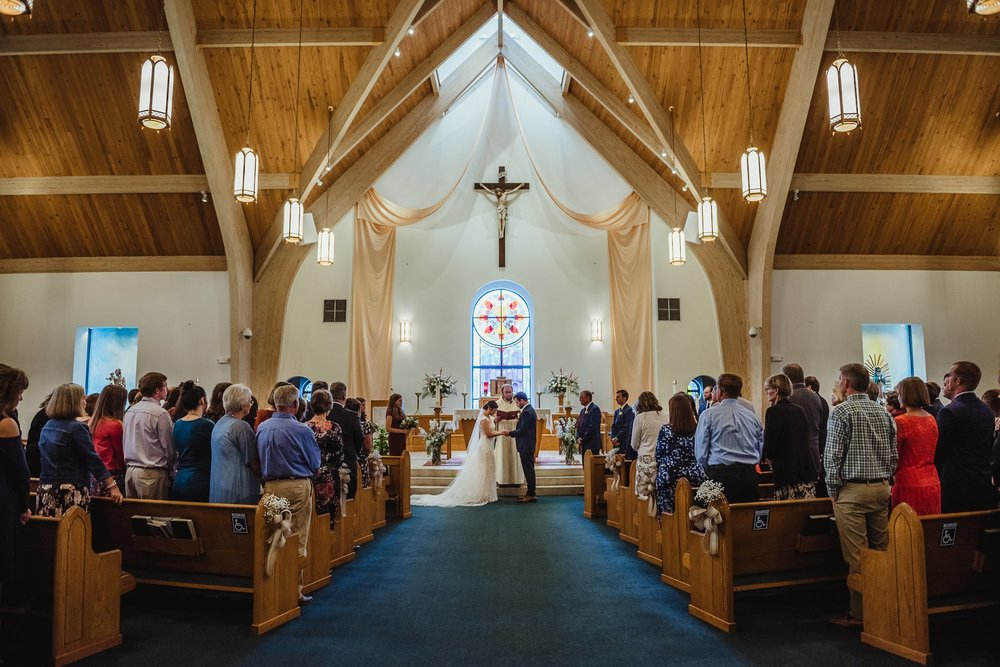 The bride and groom exchange vows at their wedding ceremony at Saint Bernadette's Catholic Church in Fuquay Varina, North Carolina. Photo by Rose Trail Images.