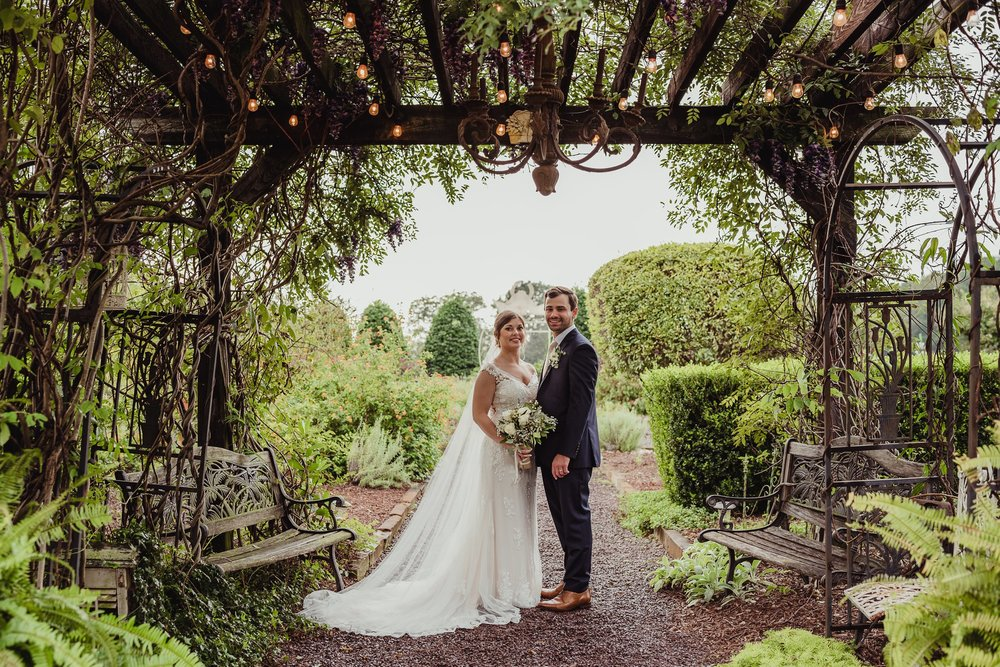 The bride and groom stand underneath the chandelier outside at the Little Herb House in Raleigh, North Carolina. Photos by Rose Trail Images.