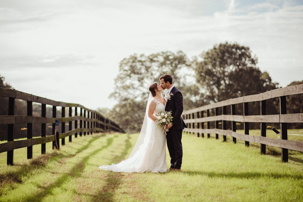 The bride and groom kiss during pictures outside before their wedding reception at the Little Herb House in Raleigh, North Carolina. Photos by Rose Trail Images.