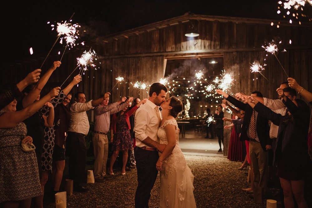 The bride and groom kiss during their sparkler exit after their wedding reception at the Little Herb House in Raleigh, North Carolina. Photos by Rose Trail Images.