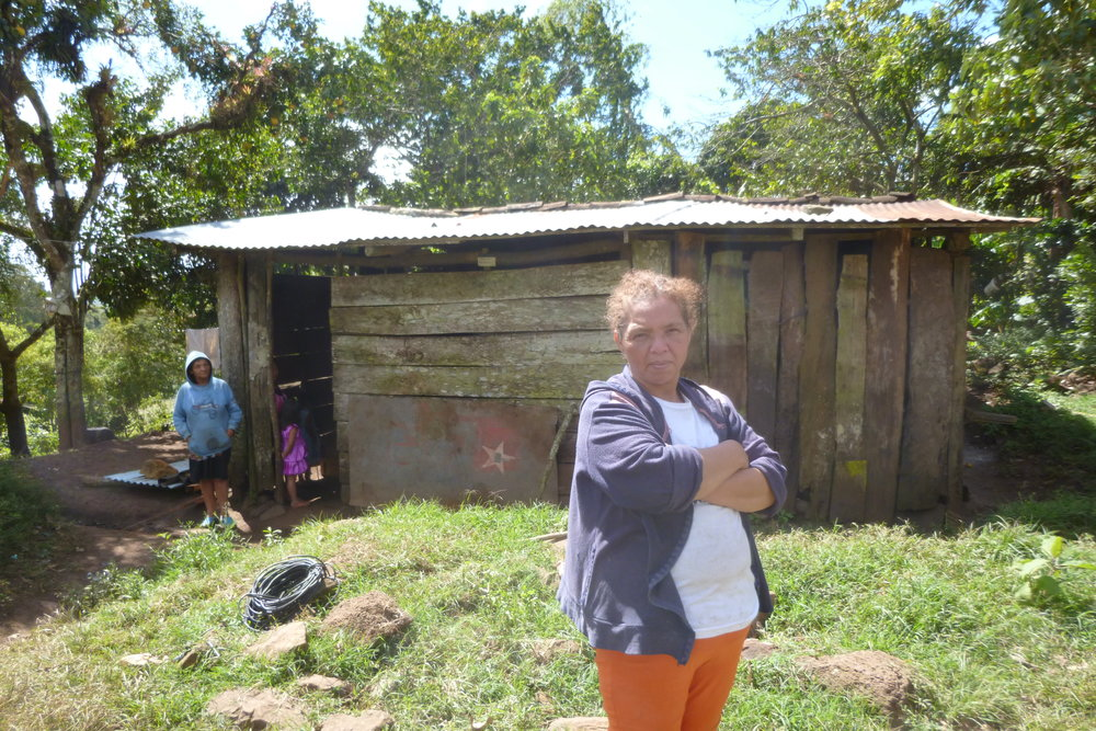 Beatriz standing in front of her house. Her neighbour and neighbour's daughter stand in the doorway.