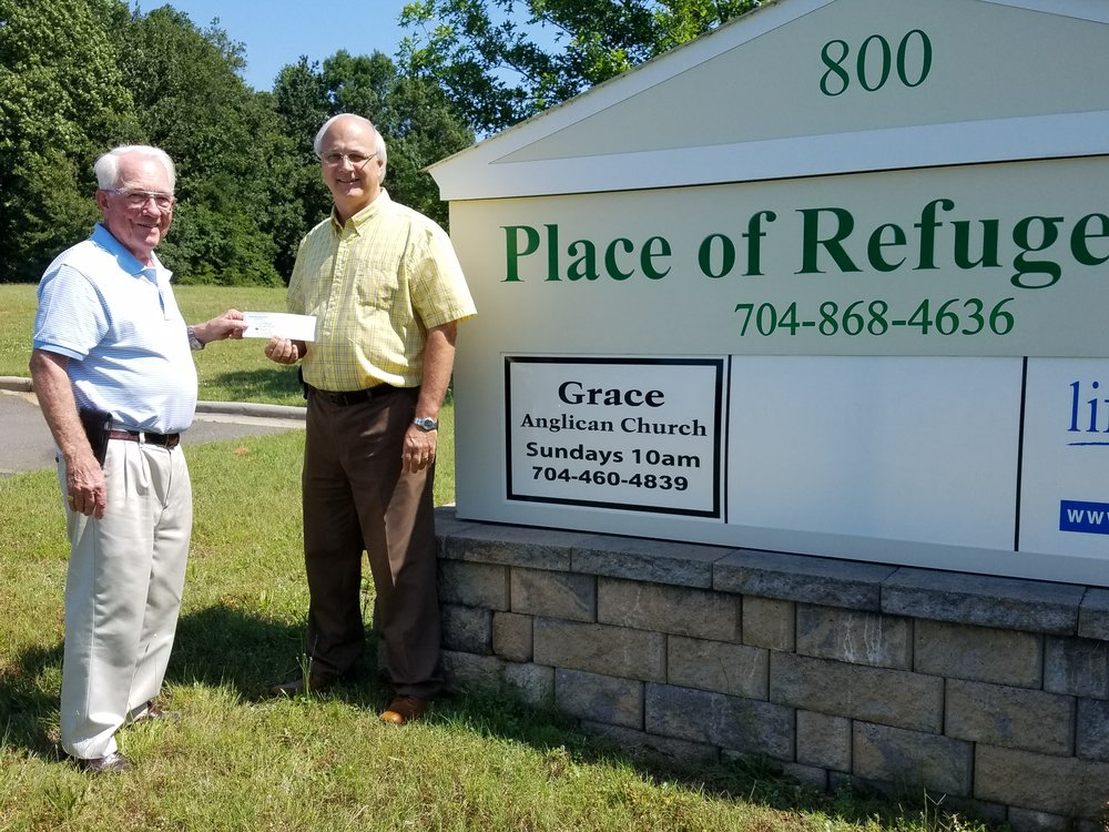 Giving Dr. Ancil Overby a check of the proceeds from our yard sale