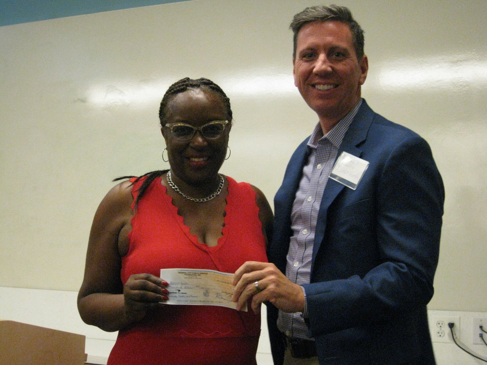Kay Henley, Chairperson Federal City Public Service Foundation (FCPSF) presenting the 2018, $10,000 Community Grant check to Access Youth, Board of Directors' Treasurer Robert McVearry, Executive Creative Director, O2 Lab, Inc.
