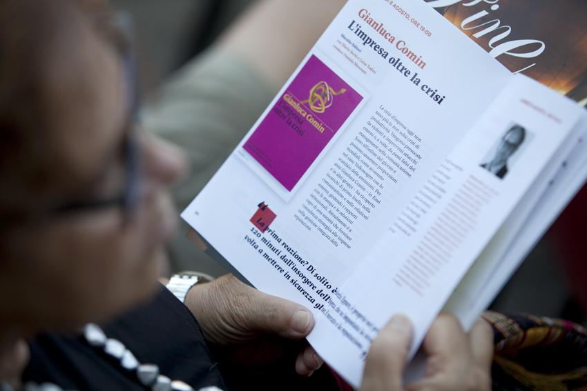 Un momento del festival in cui uno spettatore sfoglia il programma di Capalbio Libri
