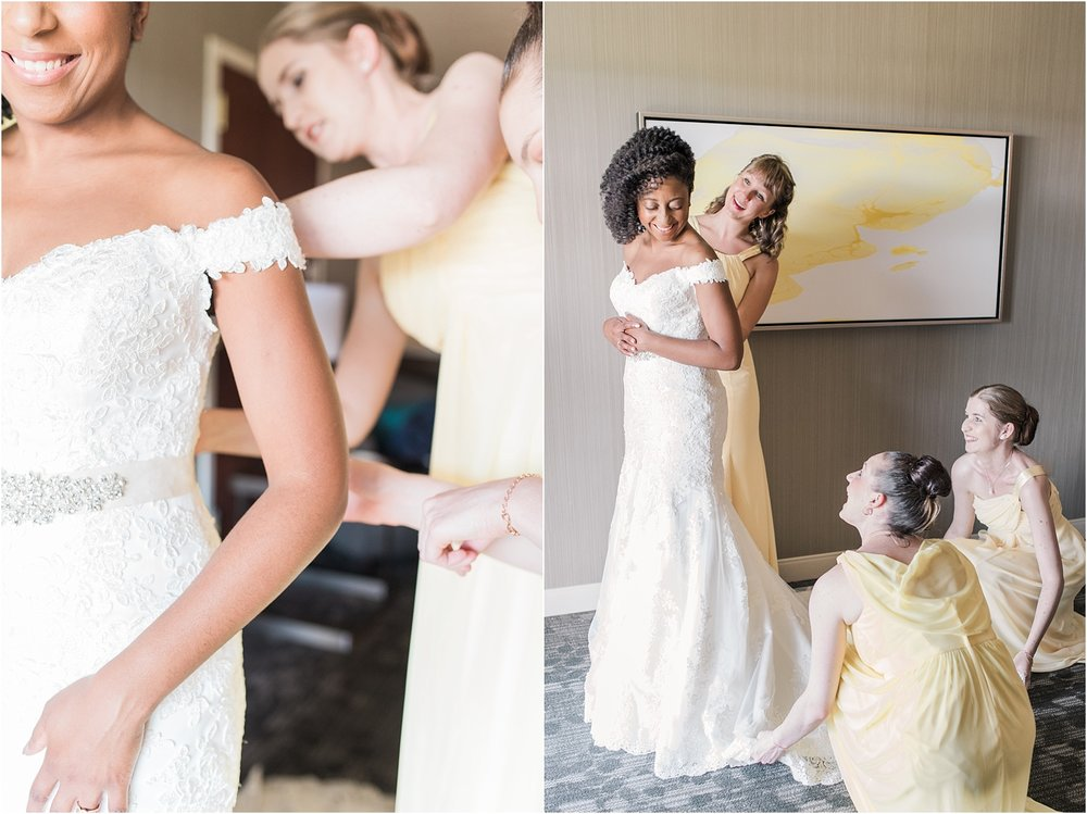 bride getting into her wedding dress with her bridesmaids.jpg