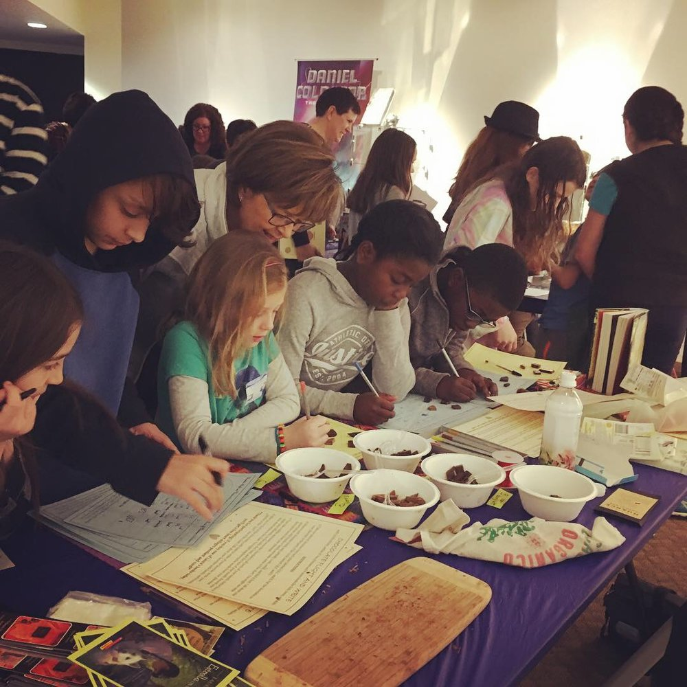Kids and teens in deep contemplation, observing chocolate with all their senses, during the chocolate-tasting I led at the Colorado Book and Arts Festival.