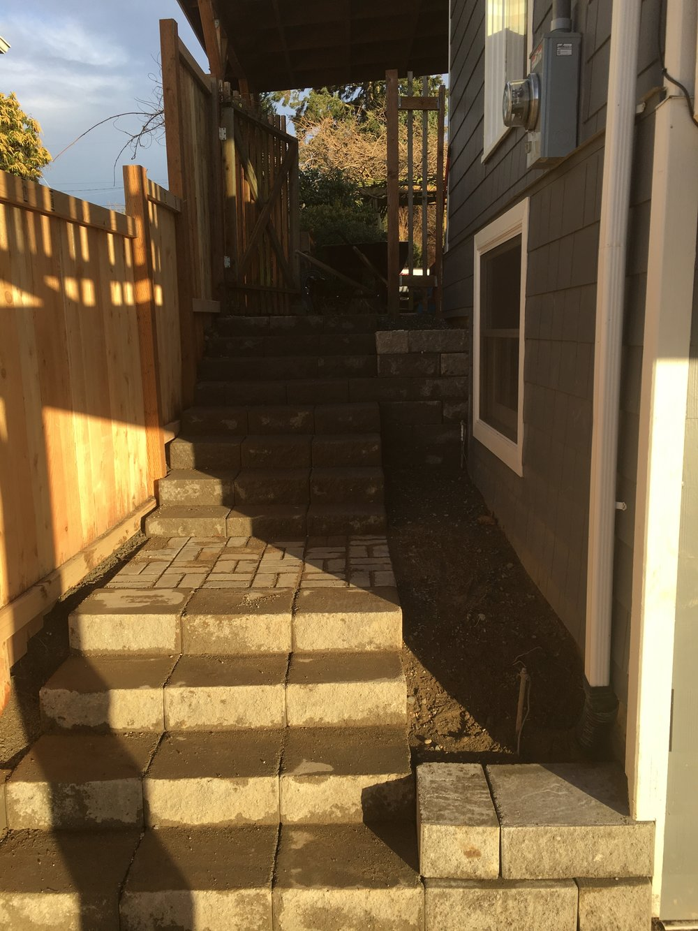 Tore down his old set of stairs and replaced them with new concrete block and retaining wall