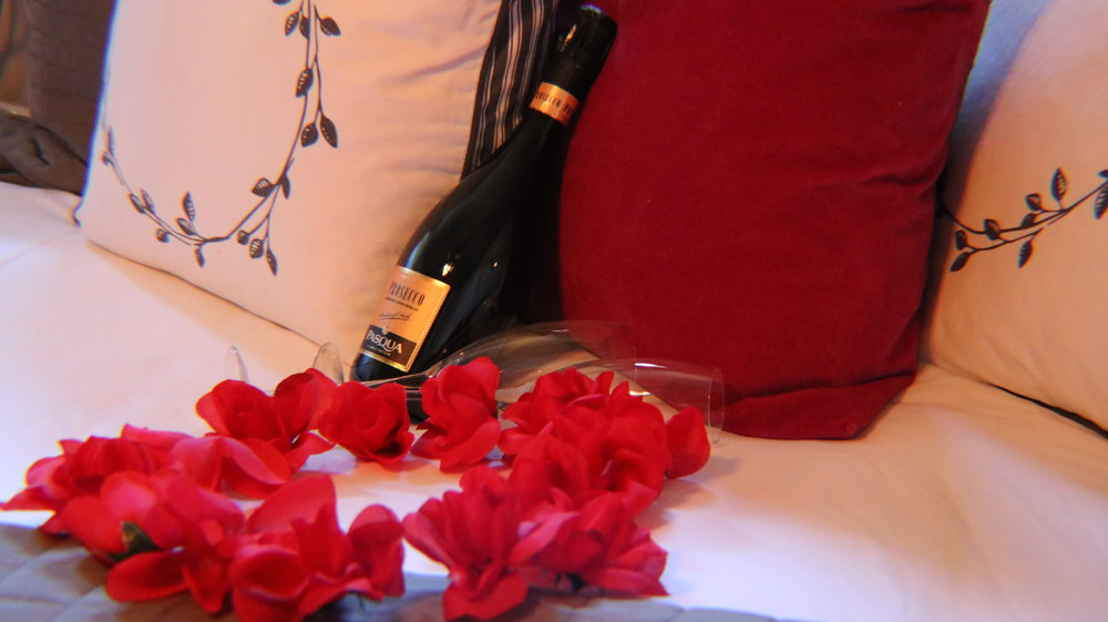 roses on bed with wine