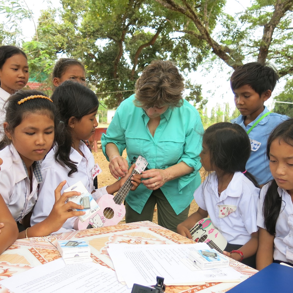 Co-founder Denise DeLong teaches a chord to a girl