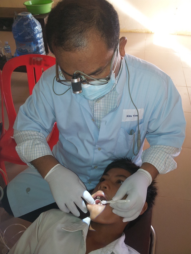 The dentist locates a boy student's cavity