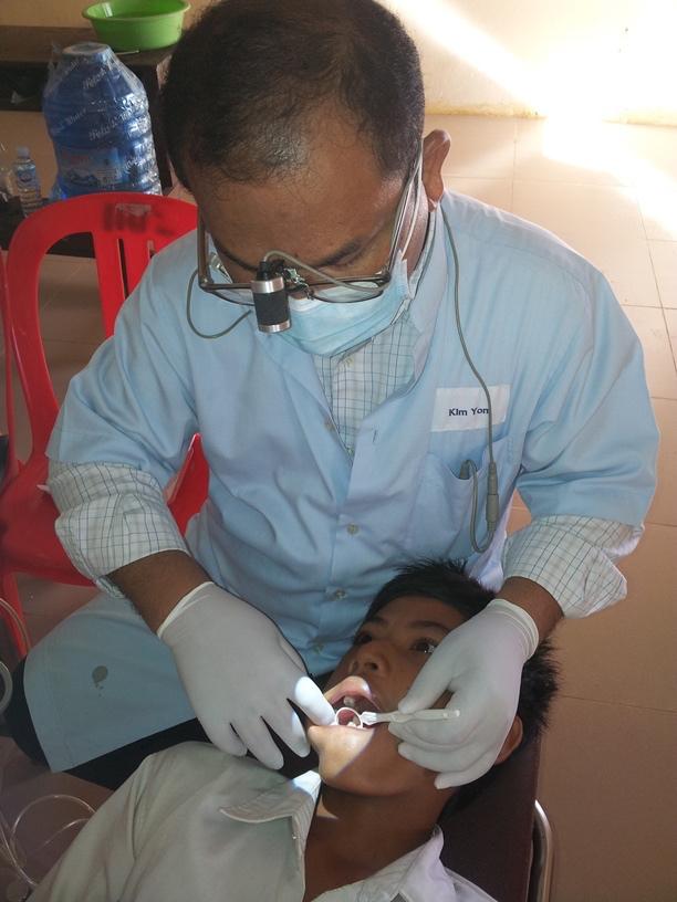 The dentist locates a boy student's cavity