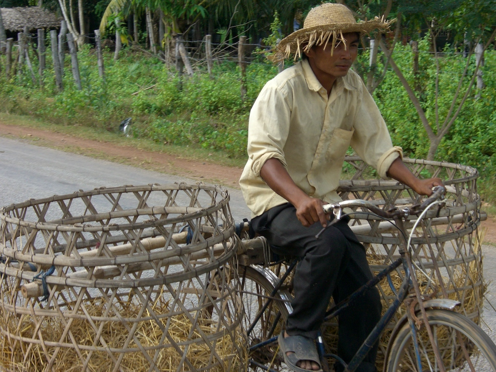 A father rides a bicycle to the market town
