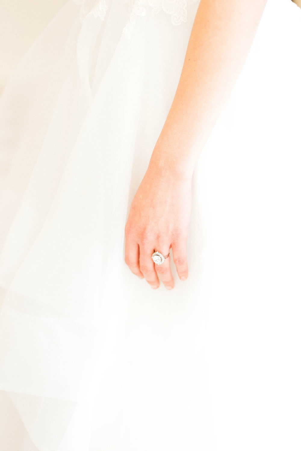 An oval engagement ring on a bride's finger