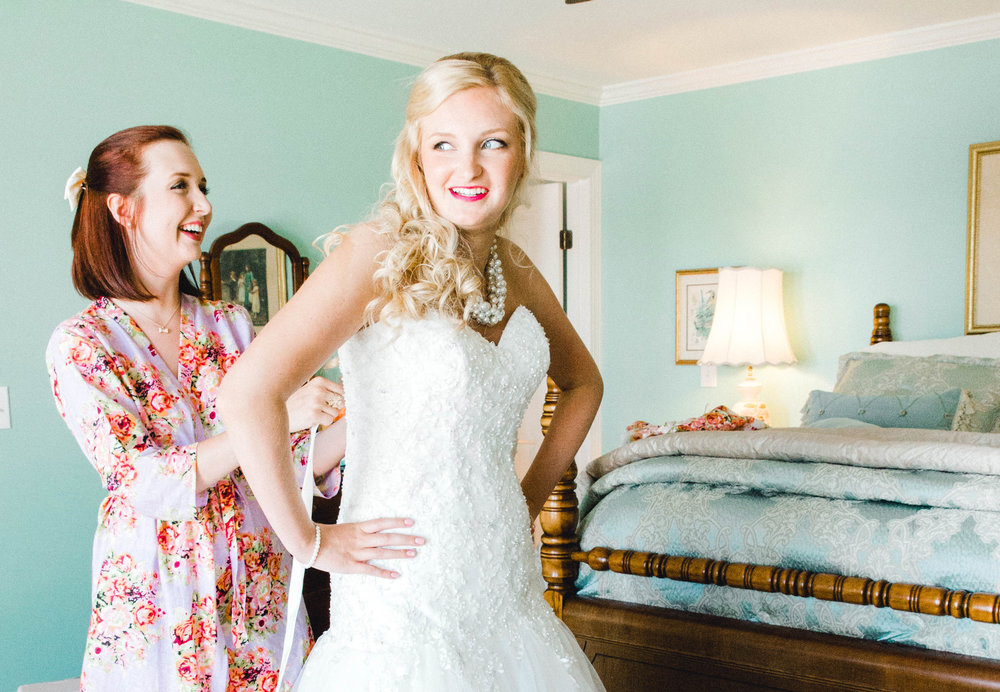A Swansboro, NC bride is putting on her wedding dress before she sees her groom.