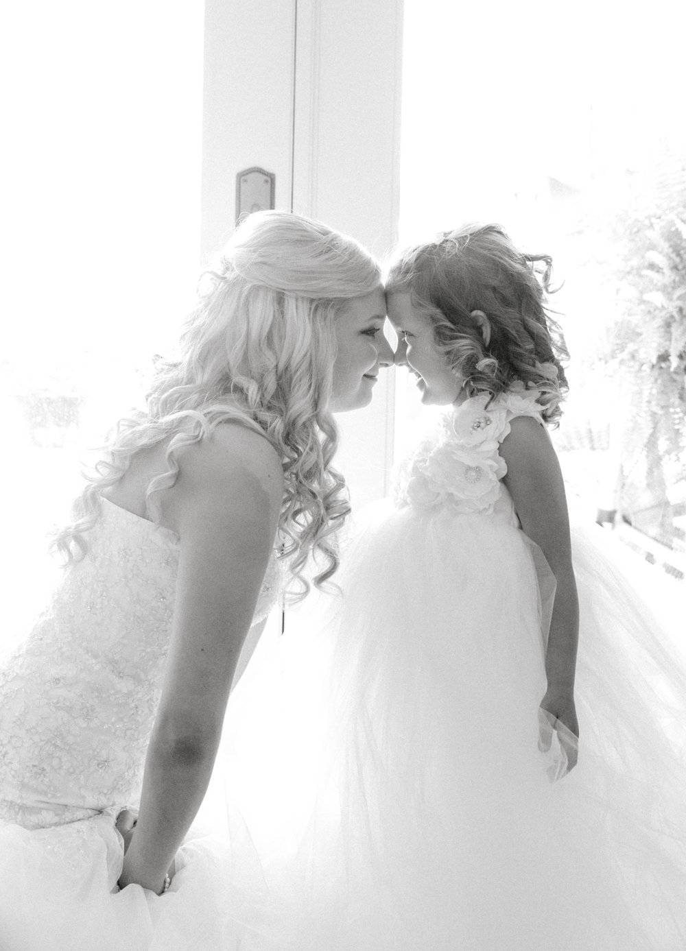 A Bride smiling at her flower girl before her wedding. Flower girl inspiration picture.