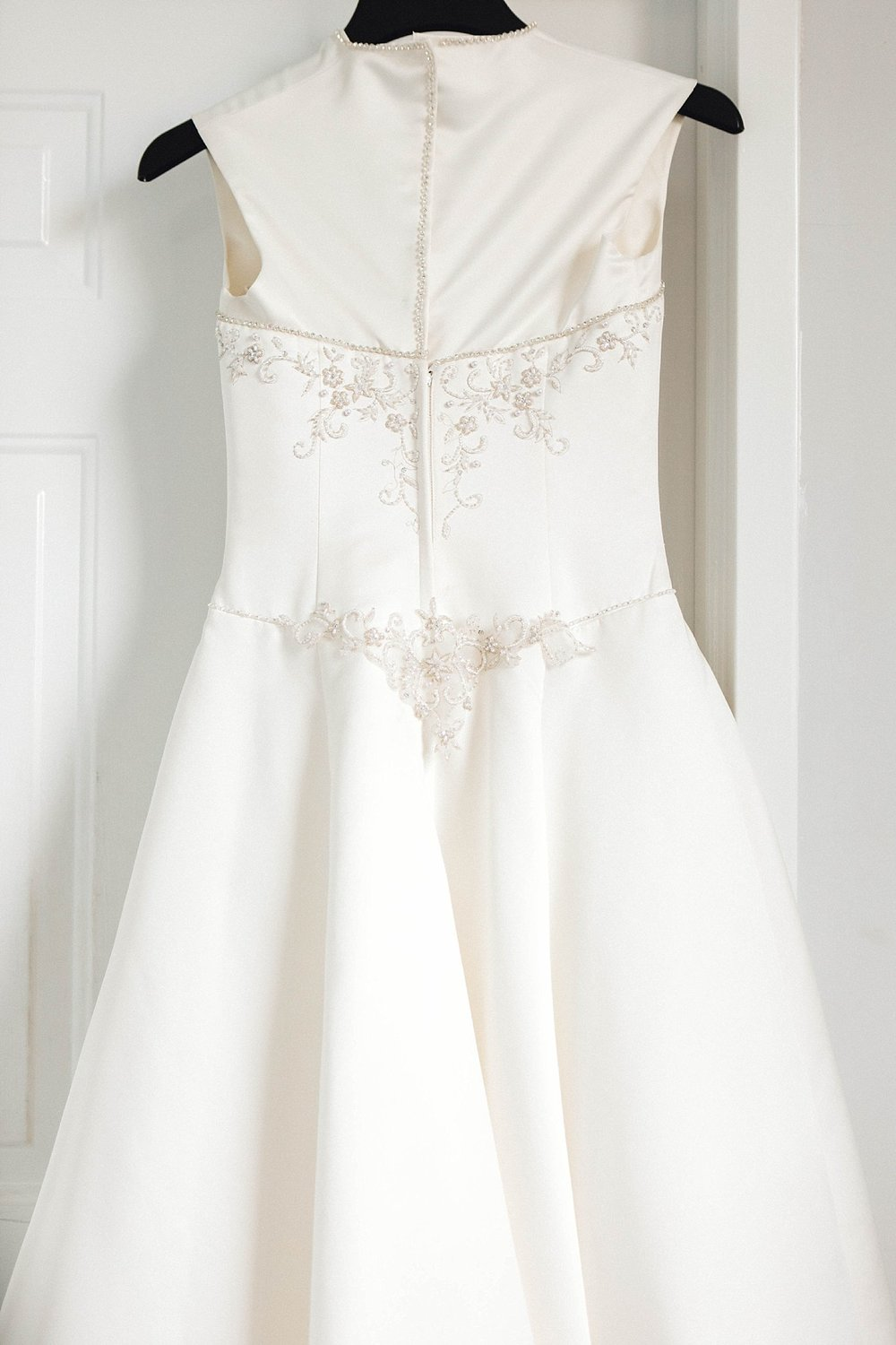 A satin wedding dress with embellishments and pearls
