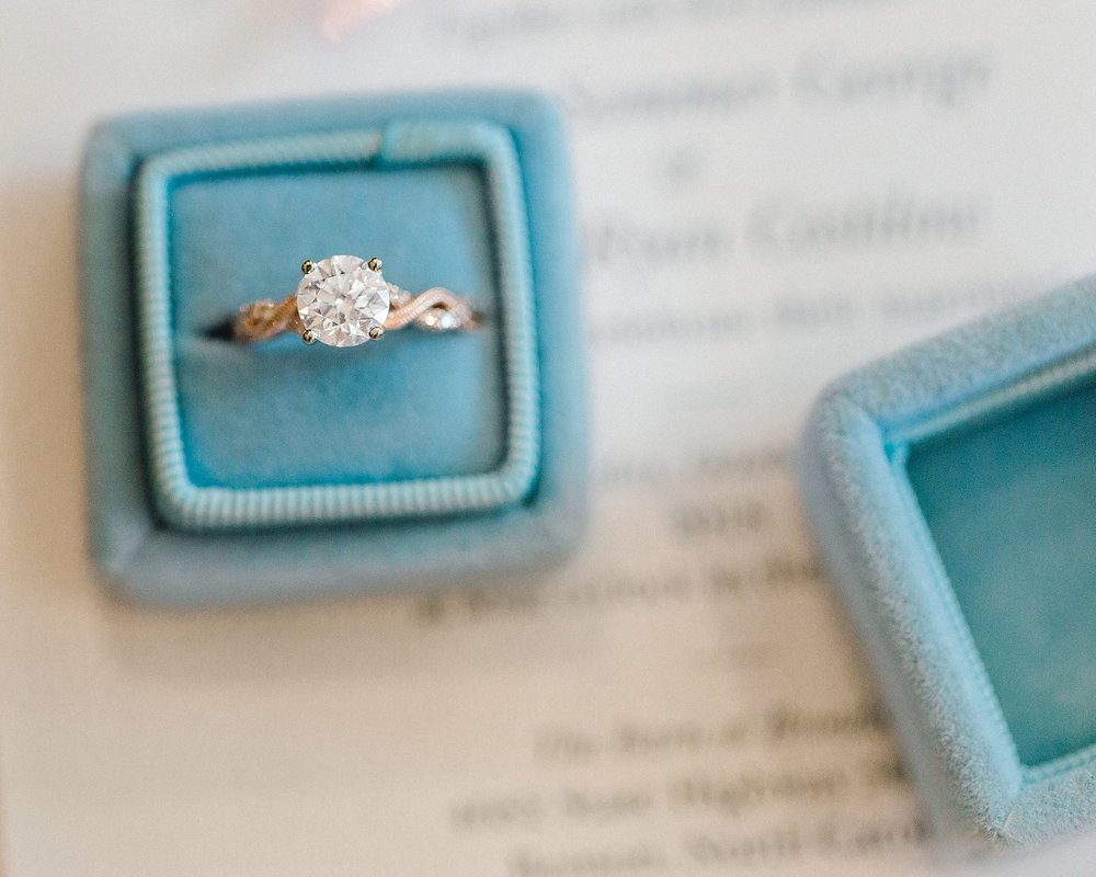 A rose gold engagement ring in a velvet ring box
