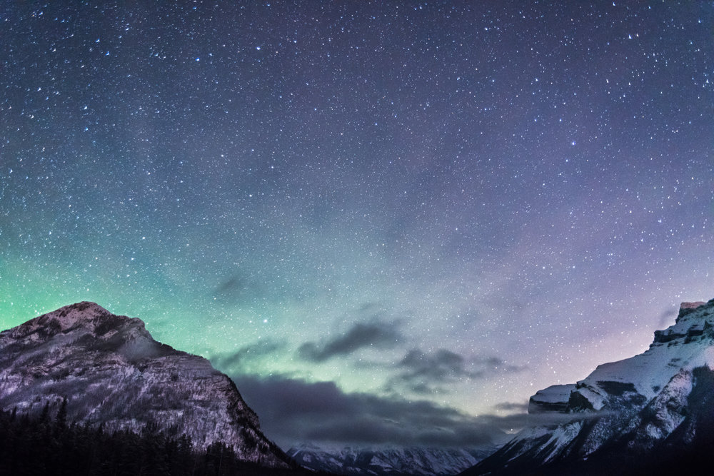 The Northern Lights helping the countless stars illuminate the night sky over the Rockies