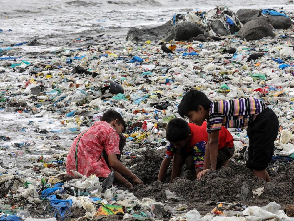 Indian children play amid leftovers and plastic waste at Mahim beach in Mumbai. Picture:EPA.