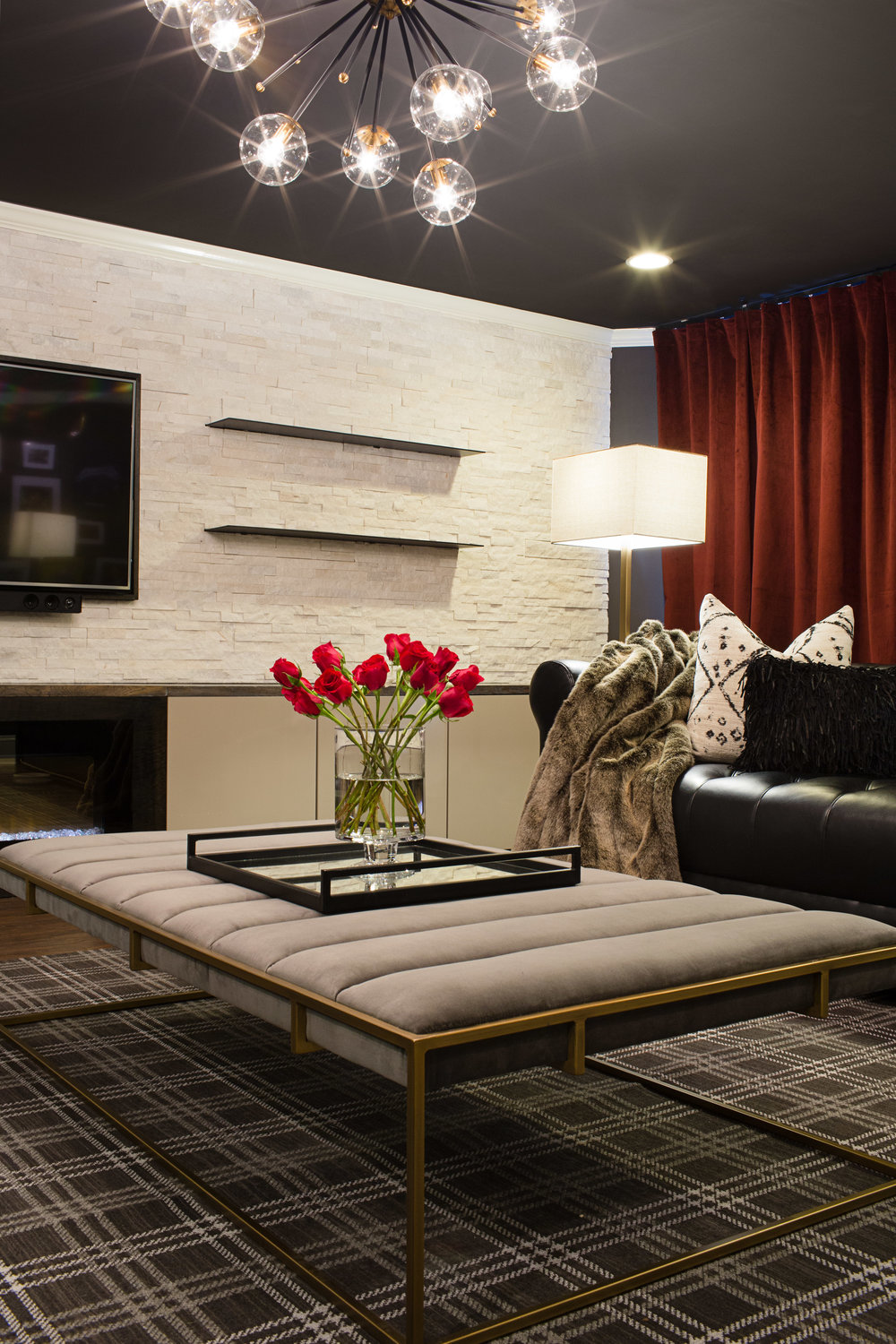 MUSIC LOVERS LOUNGE   Soul, Hip-Hop, and Rock n' Roll. This music lovers lounge is moody, with sleek black leather Chesterfield sofas, a modern Plaid rug, wall-to-wall red velvet curtains, and warm brass metals. Steel shelves cantilever through a stone wall which introduces a natural element at the room's center.