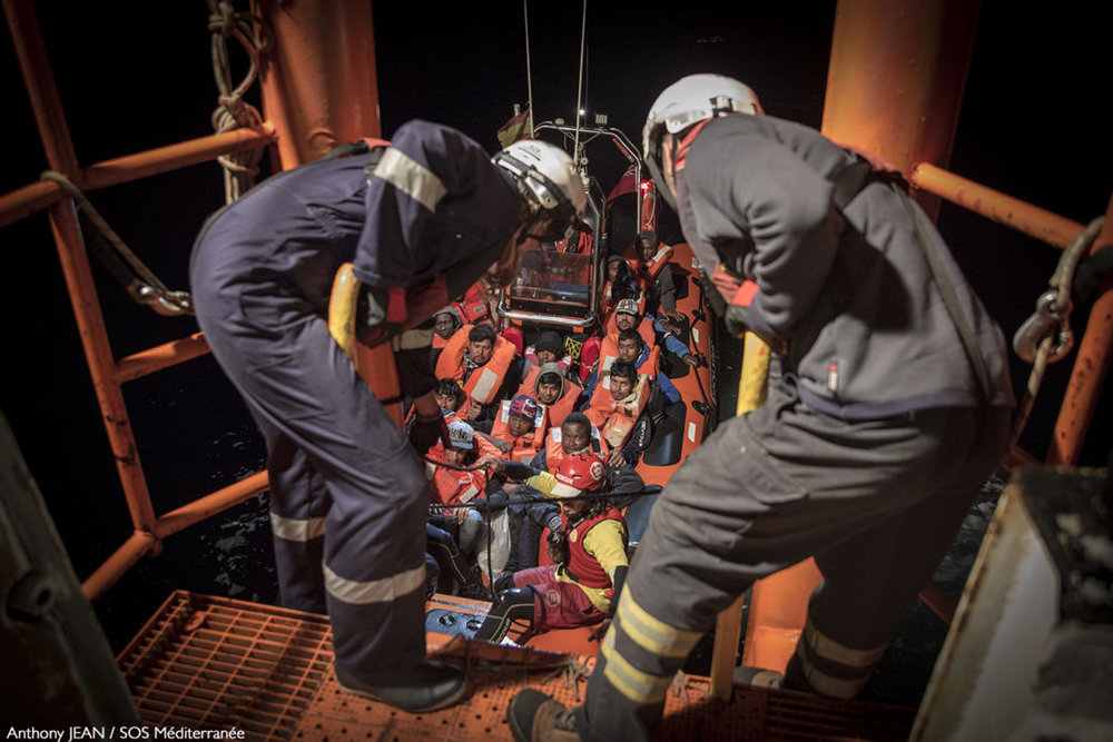 Rescuers aiding a boat loaded with migrants that recently approached Italy's shores. (Photo: SOS Méditerranée)