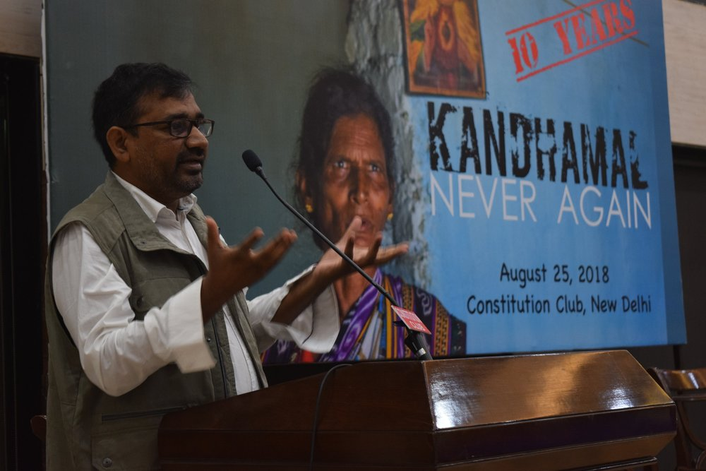 "Father Ajaya Singh speaks to an audience gathered in Delhi for ""Kandhamal Day"""