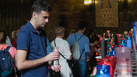 Miguel Angel Hurtado lights a candle for the patron saint, called Our Lady of Montserrat, of Catalonia, Spain.