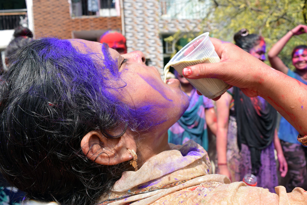 A woman drinks bhang thandai on her roof in Delhi on Holi Mar. 21, 2019. Photo by Meagan Clark.