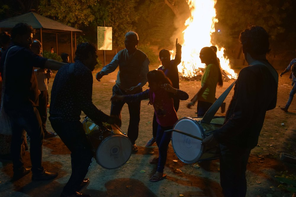 A young girl dances with her family to drum beats in front of a bonfire on Mar. 20, 2019, the night before Holi. More than 100 people gathered from an urban village in Delhi to pray their internal evil will burn away like Holika, the sister of a demon, was put to death in Hindu scriptures. Photo by Meagan Clark.