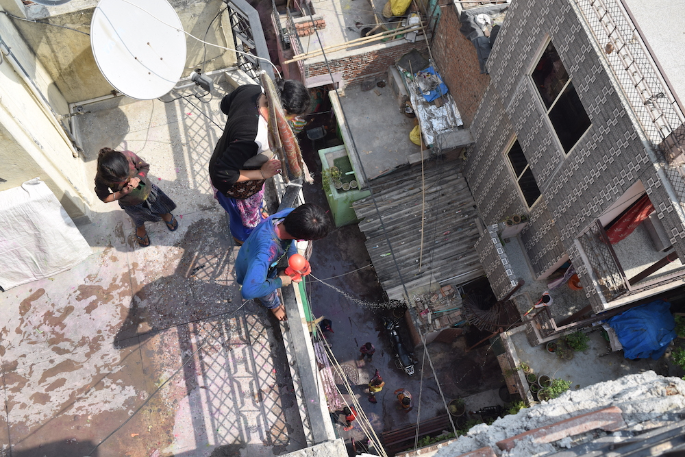 A boy shoots water onto his neighbors in Delhi three stories below as part of Holi celebrations. Photo by Meagan Clark.
