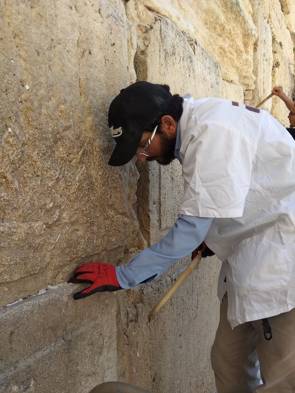 A man cleaning the Western Wall. Photo by Gil Zohar.