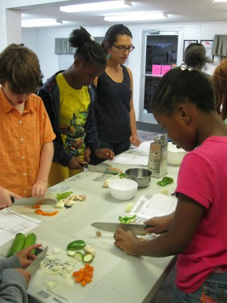 Class participants safely cutting up vegetables for their meal!
