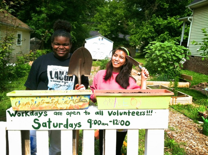 Interns Chamiya Philip and Kea Ksor welcome volunteers through their newly contracted entrance gate at the Langley Community Garden in Durham.