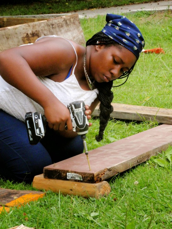 Serina Akin using a power drill to build raised vegetable beds at the Langley Garden in Durham.
