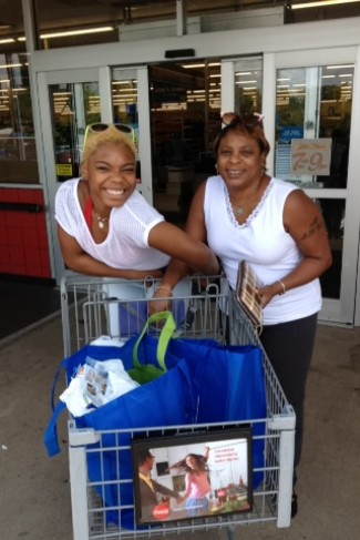 Asia Horton (left) and a friend smiling with healthy groceries they purchased for under $10.
