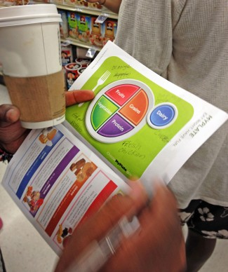 A participant uses the MyPlate graphic to plan what healthy food items he will buy during the $10 Challenge at the end of the tour.